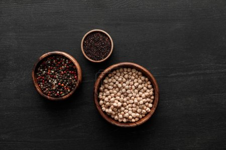 Photo for Top view on brown bowls with peppercorns, black quinoa and chickpea on dark wooden surface - Royalty Free Image