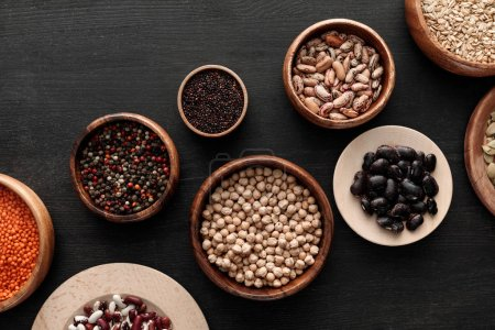 Photo for Top view of bowls with beans, chickpea, lentil, peppercorns, quinoa and oatmeal on dark wooden surface - Royalty Free Image