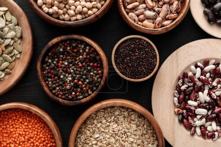 Photo for Top view of diverse wooden bowls with uncooked legumes and cereals on dark surface - Royalty Free Image