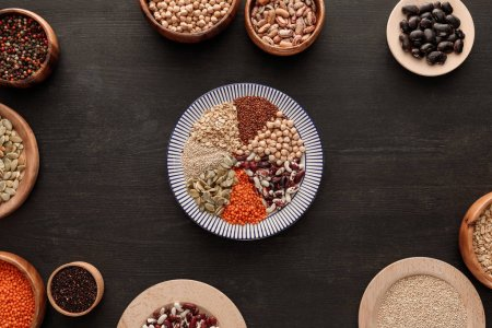 Photo for Top view of striped plate with various raw legumes and cereals near bowls on dark wooden surface - Royalty Free Image