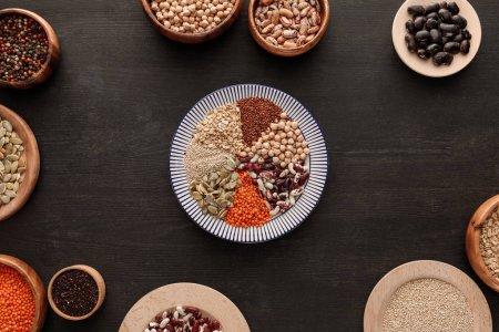 Photo pour Vue de dessus de la plaque rayée avec diverses légumineuses crues et céréales près des bols sur une surface en bois sombre - image libre de droit