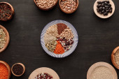 """Постер, картина, фотообои """"top view of striped plate with various raw legumes and cereals near bowls on dark wooden surface"""""""