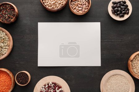 Photo for Blank white paper on dark wooden surface with bowls with cereals and legumes - Royalty Free Image