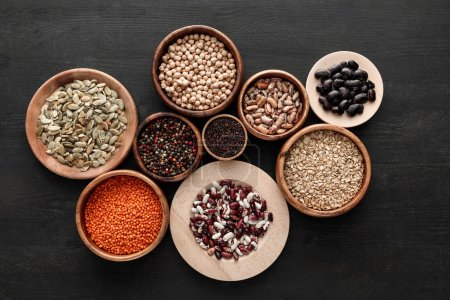 Photo for Top view of various wooden plates and bowls with beans, cereals, spice and pumpkin seeds on dark wooden table - Royalty Free Image