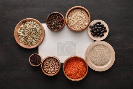 Photo for Top view of blank white paper near various wooden plates and bowls with beans, cereals, spice and pumpkin seeds on dark wooden table - Royalty Free Image