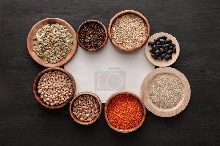Photo pour Vue du dessus du papier blanc vierge près des assiettes et bols en bois avec haricots, céréales, épices et graines de citrouille sur la table en bois sombre - image libre de droit