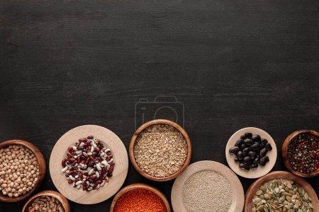 Photo pour Vue de dessus des haricots crus, des céréales, des épices et des graines de citrouille dans des bols sur une surface en bois sombre avec espace de copie - image libre de droit