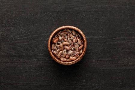Draufsicht auf braune Schale mit rohen Bohnen auf dunkler Holzoberfläche mit Kopierraum