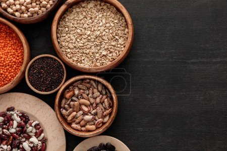 Photo for Top view of brown bowls with raw beans, lentil, oatmeals and quinoa on dark wooden surface with copy space - Royalty Free Image