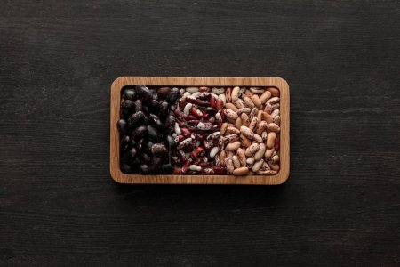 Photo for Top view of rectangular brown bowl with raw assorted beans on dark wooden surface with copy space - Royalty Free Image
