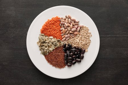 Photo for Top view of white ceramic plate with raw assorted beans, cereals and seeds on dark wooden surface with copy space - Royalty Free Image