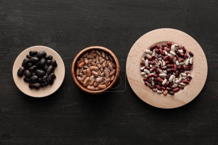Photo for Top view of bowl and plates with raw assorted beans on dark wooden surface with copy space - Royalty Free Image