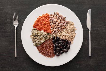 Photo for Top view of fork and knife near white ceramic plate with raw assorted beans, cereals and seeds on dark wooden surface with copy space - Royalty Free Image
