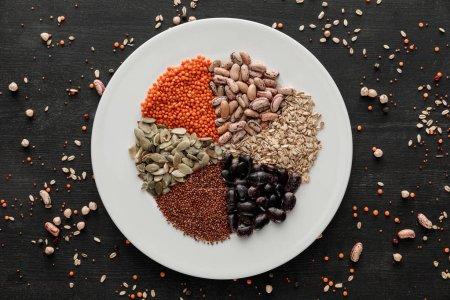 Photo pour Vue de dessus de la plaque de céramique blanche avec des haricots, des céréales et des graines crus assortis sur une surface en bois sombre avec des grains épars - image libre de droit