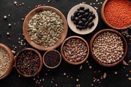 Photo for Top view of wooden bowls and plates with raw assorted beans, cereals and seeds on dark surface with scattered grains - Royalty Free Image