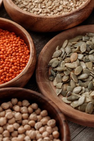 Photo for Close up view of wooden bowls with chickpea, lentil, oatmeal and pumpkin seeds - Royalty Free Image