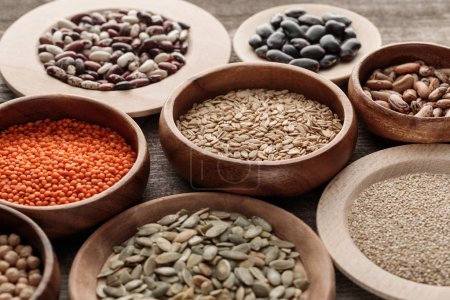 Photo for Wooden bowls with raw oatmeal, red lentil, various beans, quinoa and pumpkin seeds - Royalty Free Image