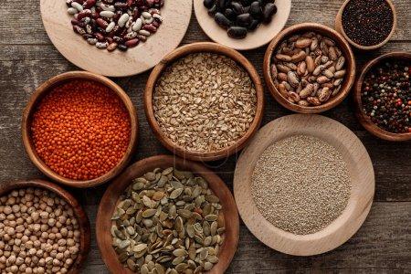 Photo pour Vue du dessus des bols avec flocons d'avoine crus, lentilles rouges, haricots divers, quinoa, pois chiches, grains de poivre et graines de citrouille sur la surface en bois - image libre de droit