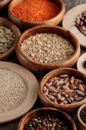 Photo pour Divers bols en bois avec haricots, graines de citrouille, lentilles et céréales - image libre de droit