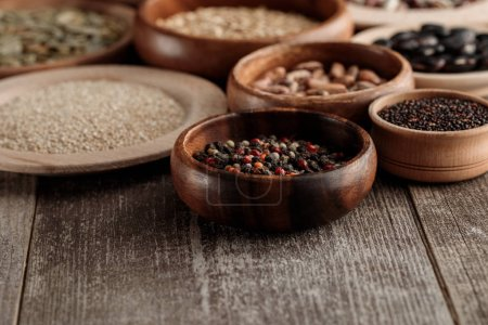 Photo for Wooden bowls and plates with peppercorns, grains and beans on brown table - Royalty Free Image