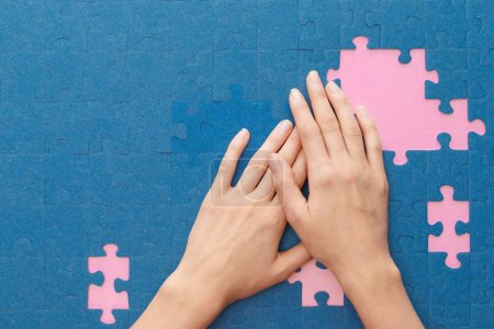Foto de Cropped view of woman covering blue jigsaw puzzle on pink background - Imagen libre de derechos