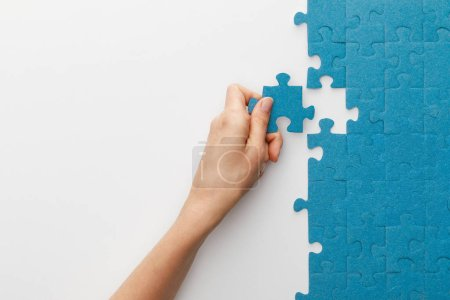 Photo for Cropped view of woman attaching blue jigsaw puzzle on white background - Royalty Free Image