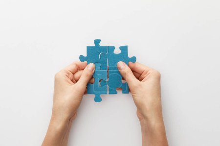 cropped view of woman holding pieces of blue jigsaw puzzle on white background