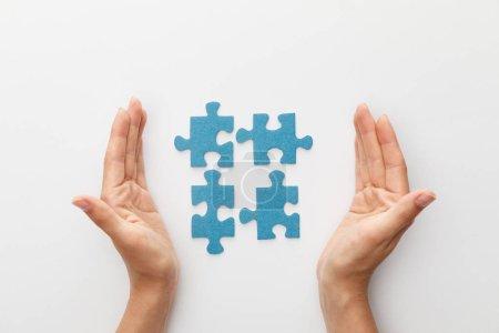 Photo pour Vue recadrée des mains de la femme près des morceaux de puzzle bleu sur fond blanc - image libre de droit