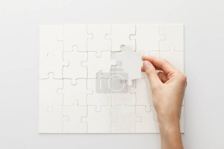 Photo for Cropped view of woman completing jigsaw puzzle on white background - Royalty Free Image