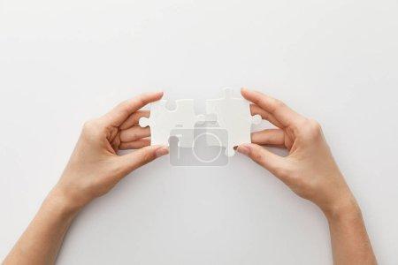 Photo pour Vue recadrée de la pièce de fixation de femme du puzzle sur le fond blanc - image libre de droit