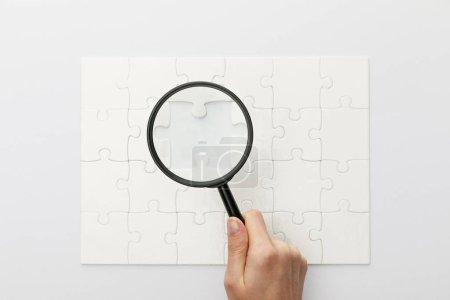 Photo pour Vue recadrée de la femme tenant loupe sous puzzle puzzle sur fond blanc - image libre de droit