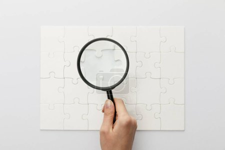 Photo for Cropped view of woman holding magnifying glass under jigsaw puzzle with lost piece on white background - Royalty Free Image