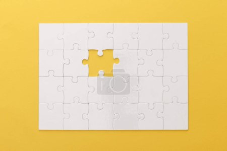Foto de Top view of white jigsaw puzzle with lost piece on yellow background - Imagen libre de derechos