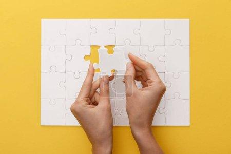 Photo pour Vue recadrée de la pièce de fixation de femme du puzzle blanc sur le fond jaune - image libre de droit
