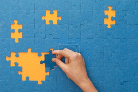 Photo for Cropped view of woman putting piece of blue jigsaw puzzle on yellow background - Royalty Free Image