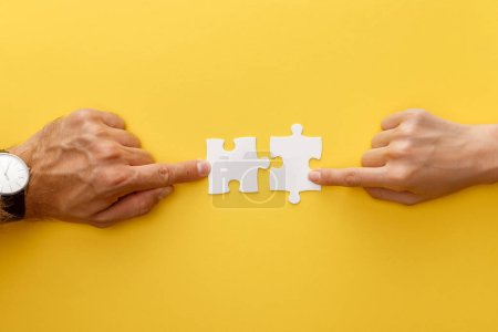 Photo for Cropped view of woman and man matching pieces of white jigsaw puzzle on yellow background - Royalty Free Image