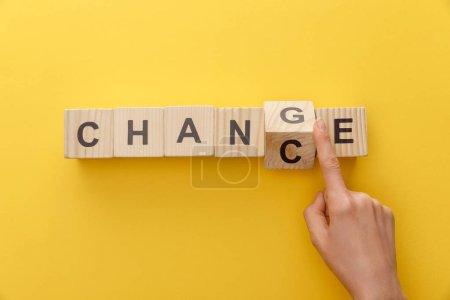 Photo pour Vue recadrée de femme changeant le cube en bois du changement de mot au hasard sur le fond jaune - image libre de droit