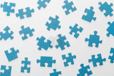 Photo pour Vue supérieure du puzzle bleu dispersé sur le fond blanc - image libre de droit