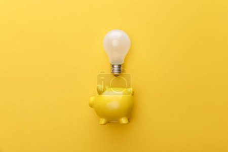 Photo pour Vue de dessus de la tirelire avec ampoule sur fond jaune - image libre de droit