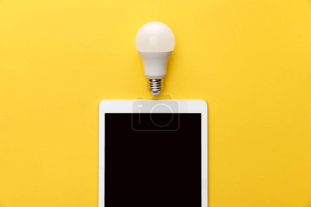 Photo for Top view of light bulb and digital tablet with blank screen on yellow background - Royalty Free Image