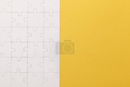 Photo pour Vue supérieure du puzzle complété blanc sur le fond jaune - image libre de droit