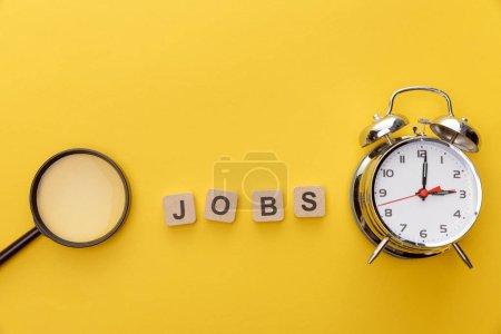 Photo pour Vue supérieure de la loupe, de l'horloge et des carrés en carton avec l'inscription d'emplois sur le fond jaune - image libre de droit