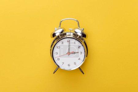 Photo pour Horloge en métal vue de dessus sur fond jaune - image libre de droit