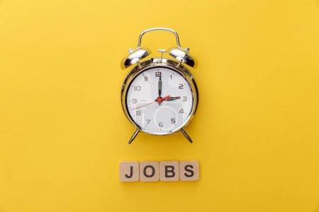 Photo pour Vue supérieure des carrés d'horloge et de carton avec l'inscription d'emplois sur le fond jaune - image libre de droit