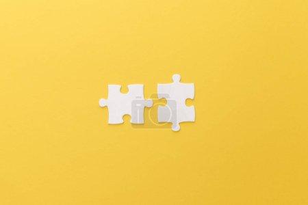 Foto de Vista superior de piezas de rompecabezas blancos sobre fondo amarillo - Imagen libre de derechos