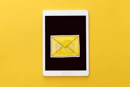 Photo pour Vue du dessus de la lettre sur tablette numérique avec écran blanc sur fond jaune - image libre de droit