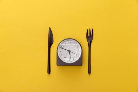 Photo pour Vue supérieure de l'horloge entre le couteau et la fourchette sur le fond jaune - image libre de droit