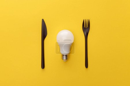 Photo for Top view of light bulb between knife and fork on yellow background - Royalty Free Image