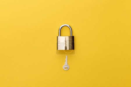Photo pour Vue de dessus du cadenas et de la clé sur fond jaune - image libre de droit