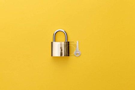 Photo pour Vue du haut du cadenas près de la clé sur fond jaune - image libre de droit